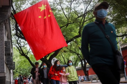 People walk past a Chinese flag near the Forbidden City during National Day holidays in Beijing, China, 5 October 2021. (Thomas Peter/Reuters)