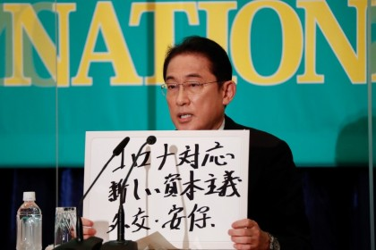 """Japan's Prime Minister Fumio Kishida, who is also the president of the ruling Liberal Democratic Party, holds up a placard reading """"Corona disease countermeasures, New Capitalism. Diplomacy and security"""" at a debate session with other leaders of Japan's main political parties ahead of the 31 October 2021 lower house election, at the Japan National Press Club in Tokyo, Japan, 18 October 2021. (Issei Kato/Reuters)"""