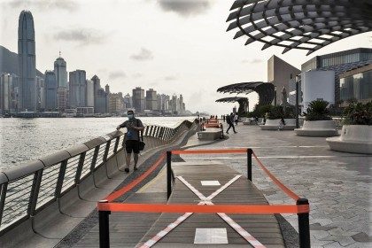 Barrier tape cordons off parts of benches to enforce safe distancing measures along the Tsim Sha Tsui waterfront in Hong Kong, on 21 April 2020. (Roy Liu/Bloomberg)