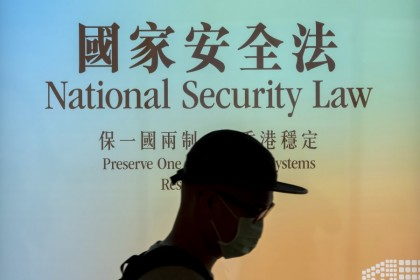 A pedestrian walks past a government-sponsored advertisement promoting a new national security law in Hong Kong, 29 June 2020. (Paul Yeung/Bloomberg)