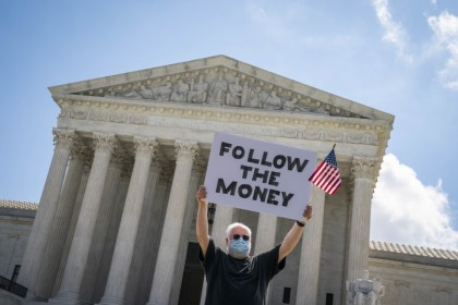"A demonstrator wearing a protective mask holds a ""Follow The Money"" sign outside the U.S. Supreme Court in Washington, 9 July 2020. The court cleared a New York grand jury to get President Donald Trump's financial records while blocking for now House subpoenas that might have led to their public release before the election. (Sarah Silbiger/Bloomberg)"