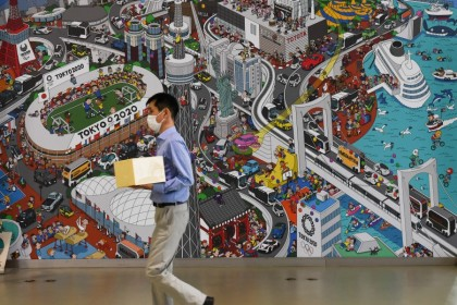A man wearing a protective face mask walks past a mural inside Toyota's Mega Web showroom in Tokyo, 4 August 2020. (Noriko Hayashi/Bloomberg)