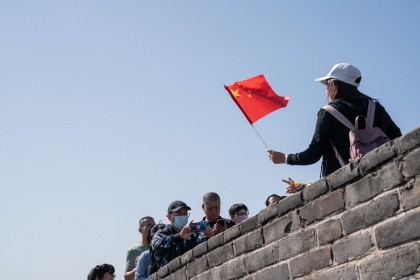 A visitor holds a Chinese flag while posing for a photograph at the Badaling section of the Great Wall in Beijing, China, on 1 October 2020. (Yan Cong/Bloomberg)