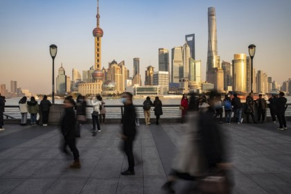 Visitors walk on the Bund in Shanghai, China, on 21 December 2020. China's central bank is striking out on its own with signals of tighter monetary policy, widening a divergence with other large economies that will shape global capital and trade flows next year. (Qilai Shen/Bloomberg)