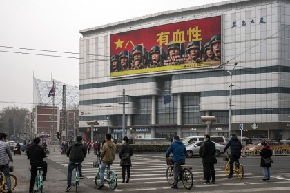 Pedestrians and cyclists stand in front of a screen showing an advertisement for the People's Liberation Army (PLA) in Beijing, China, on 5 March 2021. (Qilai Shen/Bloomberg)
