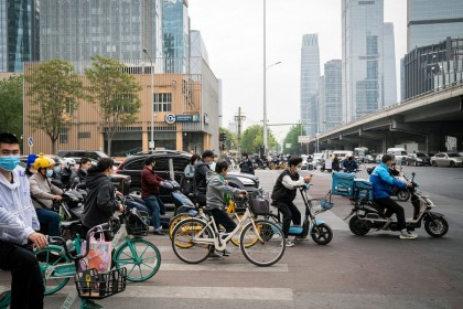 Cyclists and vehicles wait at a traffic signal light in Beijing, China on 21 April 2021. (Yan Cong/Bloomberg)