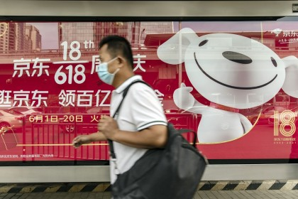 A pedestrian wearing a protective mask walks past an advertisement for China's mid-year shopping festival of JD.com in Beijing, China, 27 May 2021. (Qilai Shen/Bloomberg)