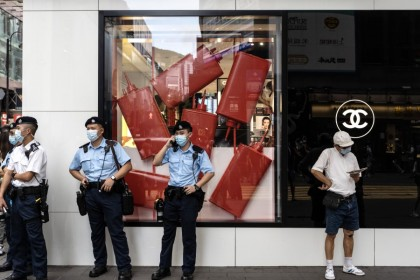 Police officers stand guard outside a Chanel Ltd. store in the Causeway Bay area of Hong Kong on 1 July 2021. Hong Kong's leader pledged to press ahead with an unprecedented national security crackdown, as the Asian financial center marked a series of fraught anniversaries symbolizing Beijing's tightening grip over local affairs. (Chan Long Hei/Bloomberg)