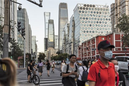 Pedestrians cross a traffic intersection near commercial buildings in Beijing, China, 25 August 2021. (Qilai Shen/Bloomberg)
