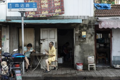 """Two men have their breakfast on the street in an older neighborhood in Shanghai, China on 30 August 2021. Chinese President Xi Jinping chaired a high-level meeting that """"reviewed and approved"""" measures to fight monopolies, battle pollution and shore up strategic reserves, all areas that are crucial to his government's push to improve the quality of life for the nation's 1.4 billion people. (Qilai Shen/Bloomberg)"""