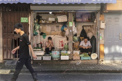 Vendors sell vegetables at a stall in an older neighborhood in Shanghai, China, on 30 August 2021. (Qilai Shen/Bloomberg)
