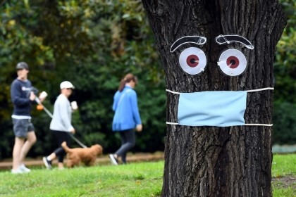 People walk past a tree with a mask and eyes stapled on it, in Melbourne, on 20 April 2020. (William West/AFP)