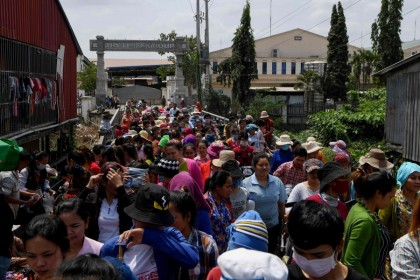 Cambodian workers exit their factory as they take a lunch break in Phnom Penh, March 2, 2020. Cambodia's multi-billion-dollar garment industry is at risk of chain disruption from the Covid-19 breakout, as its impacts hammer on Southeast Asia's key industries. (Tang Chhin Sothy/AFP)