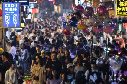 Pedestrians in a crowded street surrounded by small shops in the city of Changsha, China's Hunan province, 7 September 2020. (Hector Retamal/AFP)