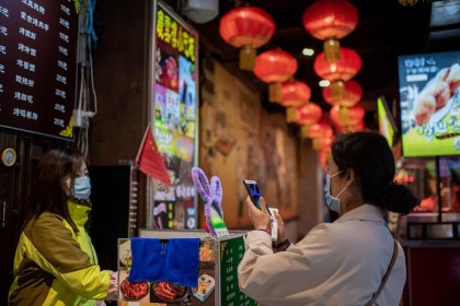 This picture taken on 28 October 2020 shows a customer (right) scanning a QR payment code (centre in green) to pay at a restaurant in Beijing, China. (Nicolas Asfouri/AFP)