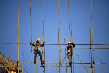The Chinese government has made efforts to curb the number of white elephant projects in China. In this photo, workers balance on scaffolding at a construction site in Beijing on 14 April 2021. (Photo by Noel Celis / AFP)