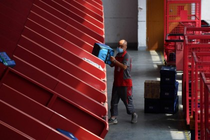 A worker collects a package after it was delivered by an automated conveyer belt at a JD.com distribution center in Beijing on 16 July 2020. (Greg Baker/AFP)