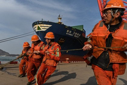 Workers pull a rope as a cargo ship carrying containers docks at the Lianyungang Port Container Terminal in Lianyungang, Jiangsu province, China on 24 March 2021. (Hector Retamal/AFP)