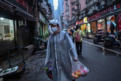 A person carries groceries in a neighbourhood in Wuhan, April 20, 2020. (Hector Retamal/AFP)