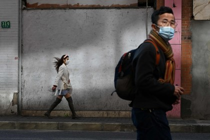 People wearing protective face masks walk along a street in Shanghai on 17 February 2020. (Noel Celis/AFP)