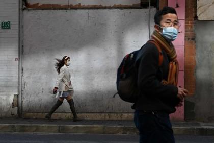 People wearing protective face masks walk along a street in Shanghai on 17 February 2020. (Noel Celis/AFP)