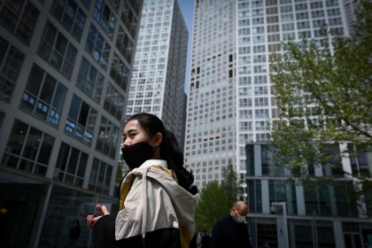 A woman wearing a face mask walks in the Central Business District in Beijing on 14 April 2020. (Wang Zhao/AFP)