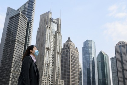 "As the world's second largest economy, China should have gained enough confidence to not be affected by terms like ""sick man of Asia"". In this photo taken on 25 February 2020, a woman wearing a protective face mask walks on an overpass in Shanghai. (Noel Celis/AFP)"
