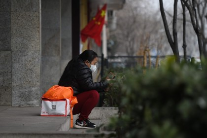 A woman wears a face mask as a preventive measure against the Covid-19 coronavirus as she looks at her mobile phone near the entrance of the Peking University People's Hospital in Beijing on 21 February 2020. (Greg Baker/AFP)