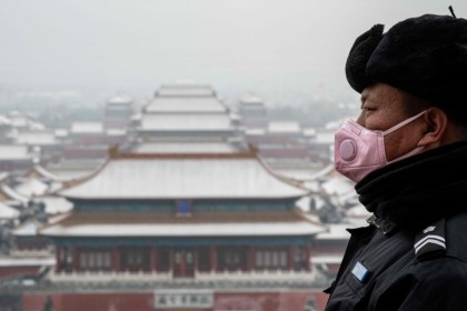 A security guard in a mask looks out from the Jingshan park overlooking the Forbidden city (center) after a snowfall in Beijing, February 2020. (Nicolas Asfouri/AFP)