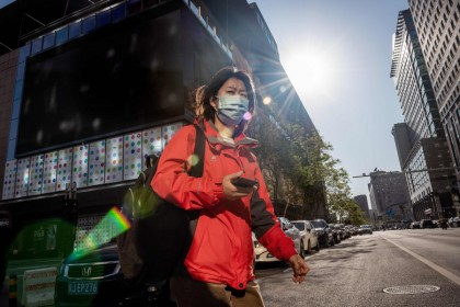 A woman crosses a street in Beijing, April 22, 2020. China's economy shrank for the first time in decades last quarter. (Nicolas Asfouri/AFP)