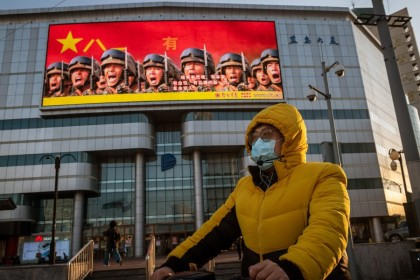 A man in front of a screen displaying a propaganda image (top), on a street in Beijing, April 20, 2020. (Nicolas Asfouri/AFP)