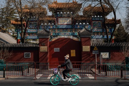 In this photo taken on 23 February 2020, a woman wearing a protective facemask to protect against the Covid-19 coronavirus cycles in front of the Lama Temple that is closed off to the public in Beijing. (Nicolas Asfouri/AFP)