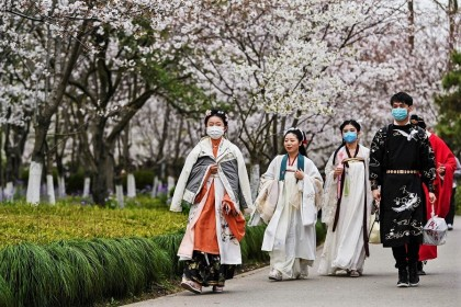Young people wearing face masks amid concerns over the Covid-19 coronavirus walk dressed in Tang Dynasty costumes at Century Park in Shanghai on 22 March 2020. (Hector Retamal/AFP)