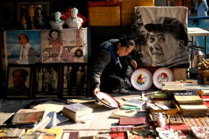 A vendor arranges books at her stall at the Panjiayuan antique market in Beijing, China, on 19 November 2020. (Noel Celis/AFP)