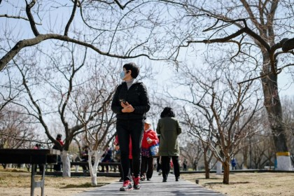 People walk in a public park under blue skies in Beijing on 16 March 2021. (Wang Zhao/AFP)