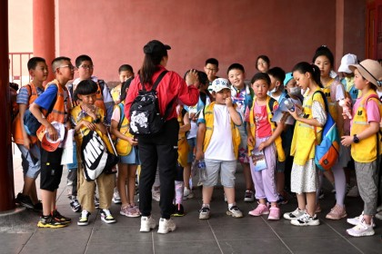 Children stand at the entrance of the Forbidden City in Beijing on 12 June 2021. (Noel Celis/AFP)