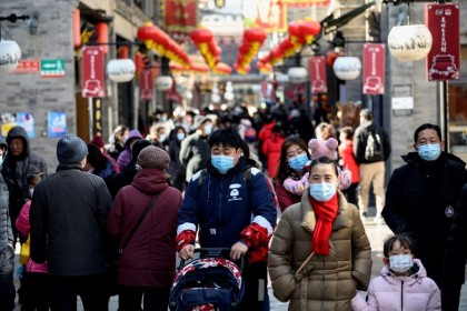People walk in Qianmen street in Beijing on 17 February 2021. (Noel Celis/AFP)