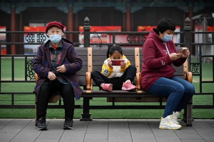 A girl uses a mobile phone as she rests on a bench in Beijing, China, on 4 March 2021. (Wang Zhao/AFP)