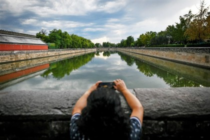 A woman uses her mobile phone to take pictures at the Forbidden City in Beijing on 1 September 2020. (Wang Zhao/AFP)