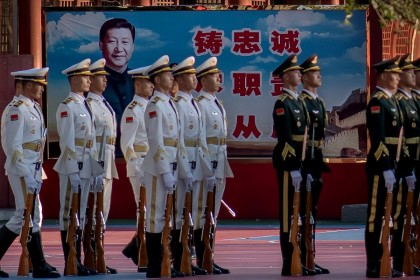 Military personnel stand in formation next to a portrait of Chinese President Xi Jinping (back) outside the Forbidden City in Beijing on 22 October 2020. (Nicolas Asfouri/AFP)