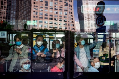 People commute on a bus during morning rush hour in Beijing on 22 May 2020. (Nicolas Asfouri/AFP)