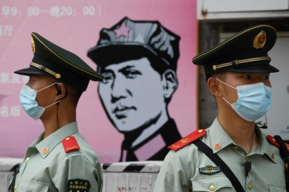 Paramilitary police officers stand guard in front of a poster of late communist leader Mao Zedong on a street south of the Great Hall of the People during the opening session of the National People's Congress (NPC) in Beijing on May 22, 2020.  (Greg Baker/AFP)