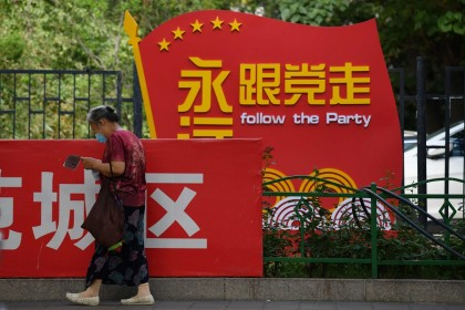 "A woman walks past a Communist Party slogan urging people to ""Follow the Party forever"" outside a residential compound in Beijing on 6 July 2020. (Greg Baker/AFP)"