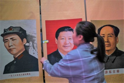 This picture taken during a government organised media tour shows a seller holding a portrait of the Chinese President Xi Jinping next to pictures of the former Chinese leader Mao Zedong at Dongfanghong Theatre in Yan'an, the headquarters of the Chinese Communist Party from 1936 to 1947, in Shaanxi province on 10 May 2021. (Hector Retamal/AFP)