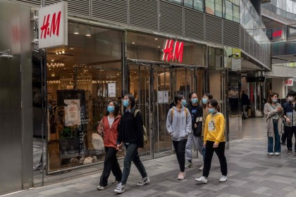 People walk past an H&M store in Beijing on 5 April 2021. (Nicolas Asfouri/AFP)