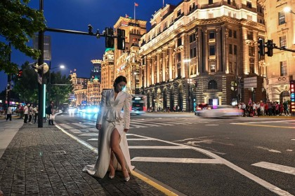 This photo taken on 25 May 2021 shows a woman posing for a picture on the Bund in Shanghai, China. (Hector Retamal/AFP)