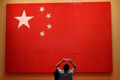 A journalist takes a picture of the national flag during a visit to the Museum of the Communist Party of China, in Beijing, China, on 25 June 2021. (Noel Celis/AFP)