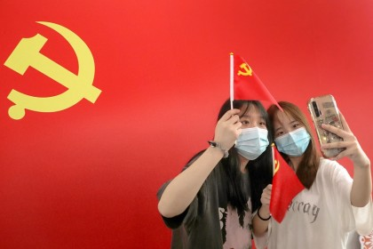 Commuters take photos with a flag of the Communist Party of China at Nantong Railway Station, Jiangsu province, China on 1 July 2021, during celebrations to mark the 100th anniversary of the founding of the Communist Party of China. (STR/AFP)