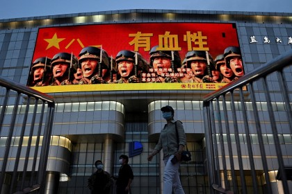 """People walk along a street in Beijing on 18 May 2021 past military propaganda which reads: """"Courageous —  raise a new generation of spirited, capable, courageous and morally upright revolutionary soldiers."""" (Noel Celis/AFP)"""
