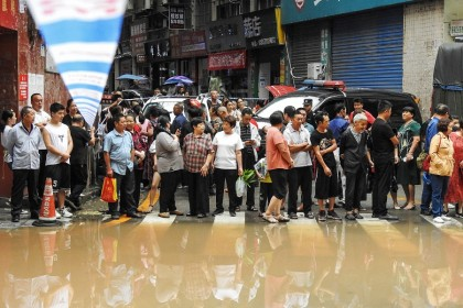 This photo taken on 6 September 2021 shows residents looking at a flooded area after heavy rainfalls in Quxian county, Dazhou city, Sichuan province, China. (STR/AFP)